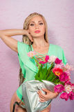 Beautiful attractive blonde young woman with african braids with tulips on pink background Royalty Free Stock Image