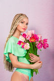 Beautiful attractive blonde young woman with african braids with tulips on pink background Stock Photo