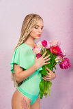 Beautiful attractive blonde young woman with african braids with tulips on pink background Royalty Free Stock Photo