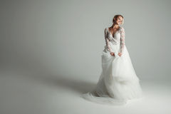 Beautiful attractive bride in wedding dress with long full skirt, white background Stock Photos