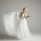 Beautiful attractive bride in wedding dress with long full skirt, white background, dance and smile Stock Photos