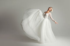 Beautiful attractive bride in wedding dress with long full skirt, white background, dance and smile Stock Photo