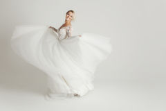Beautiful attractive bride in wedding dress with long full skirt, white background, dance and smile Royalty Free Stock Image