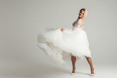 Beautiful attractive bride in wedding dress with long full skirt, white background, dance and smile Stock Photography