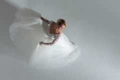 Beautiful attractive bride in wedding dress with long full skirt, white background, dance and smile, top view Stock Photo