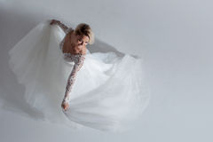 Beautiful attractive bride in wedding dress with long full skirt, white background, dance and smile, top view Royalty Free Stock Photography