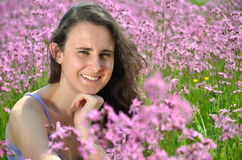 Beautiful attractive brunette girl on gorgeous meadow full of wild flowers Royalty Free Stock Photos