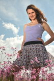 Beautiful attractive brunette girl standing on gorgeous meadow full of wild flowers Royalty Free Stock Photography