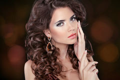 Beautiful attractive brunette woman model with wavy long hair an. D fashion earrings. Skincare Royalty Free Stock Image