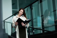 Beautiful and attractive businesswoman looking at files. While standing Royalty Free Stock Photos