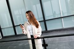 Beautiful and attractive businesswoman texting on cellphone Royalty Free Stock Images