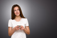 Beautiful attractive casual young woman talking on her mobile phone. Studio shot over gray background. Royalty Free Stock Images