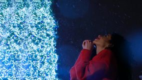 Make a wish or pray. Beautiful attractive curly woman in red standing near a new year tree with garlands peers into the night sky and falling snowflakes. New stock video
