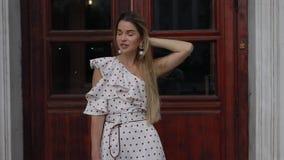 Beautiful elegant woman in dress posing at summer city. Beautiful attractive elegant woman in dress posing at summer city near brown old door stock footage