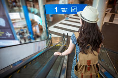 Female student arrived travel destination. Beautiful attractive female student arrived travel destination and taking the airport escalator going to transport Royalty Free Stock Image
