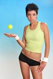 Beautiful attractive female with tennis ball. Young female with tennis ball on cyan-blue background Stock Images