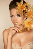 Beautiful Attractive Girl With Golden Flowers. Beauty Model Woma. N Face. Perfect Skin. Professional Make-up. Makeup Stock Photo