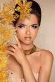 Beautiful Attractive Girl With Golden Flowers. Beauty Model Woma. N Face. Perfect Skin. Professional Make-up. Makeup Royalty Free Stock Photography