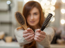 Beautiful, attractive girl with long, curly, red hair holding a hair comb, close-up. Royalty Free Stock Photo