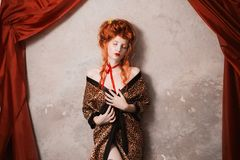 Beautiful attractive girl with red hair. A woman with red hair in leopard print gown with a gun in his hand. Red-haired girl with pale skin and blue eyes with a Stock Photography