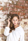 Beautiful attractive girl in white in front of old   brick wall. Beautiful attractive girl in white in front of old grunge brick wall Stock Photography