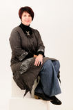 Beautiful attractive mature woman sitting in jeans Royalty Free Stock Photography