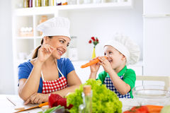 Beautiful attractive mother and child playing with vegetables Stock Images