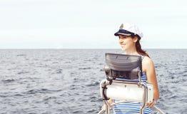 Beautiful, attractive sailor girl driving a boat. Sea, navigatio Stock Photography