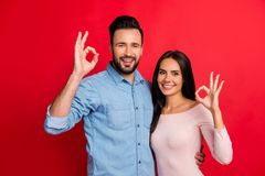 Beautiful, attractive, sexy smiling couple gesturing ok sign ove. R red background, perfect relations between wife and husband, ideal young family Royalty Free Stock Image