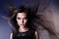 Beautiful attractive sexy young Brazilian fashion model with hair blown by the air studio shot. Wearing dress Royalty Free Stock Images