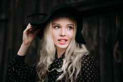 Beautiful attractive and stylish girl wearing black hat standing posing in city. Nude makeup, best daily hairstyle and great fashi Royalty Free Stock Photo