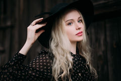 Beautiful attractive and stylish girl wearing black hat standing posing in city. Nude makeup, best daily hairstyle and great fashi Royalty Free Stock Photos