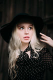 Beautiful attractive and stylish girl wearing black hat standing posing in city. Nude makeup, best daily hairstyle and great fashi Stock Photos