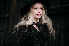 Beautiful attractive and stylish girl wearing black hat standing posing in city. Nude makeup, best daily hairstyle and great fashi Stock Image
