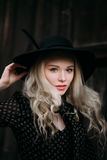 Beautiful attractive and stylish girl wearing black hat standing posing in city. Nude makeup, best daily hairstyle and great fashi Royalty Free Stock Images