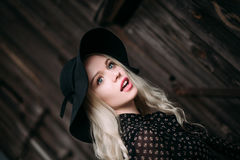 Beautiful attractive and stylish girl wearing black hat standing posing in city. Nude makeup, best daily hairstyle and great fashi Stock Images