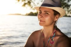 Beautiful attractive tanned young woman in hat looks at the frame on the beach on warm summer evening at sunset. Royalty Free Stock Photography