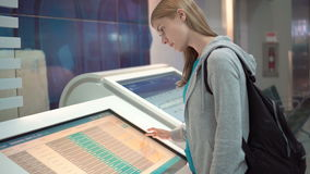 Beautiful attractive woman in airport terminal. Using touchscreen, searching for flight information. Beautiful attractive young woman in airport terminal. Using stock video footage