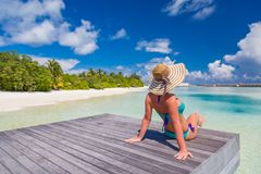 Beautiful attractive woman in bikini and hat lying on beach wooden jetty and luxury water villa. Sea view, luxury lifestyle Royalty Free Stock Photography