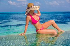 Beautiful attractive woman in bikini and hat lying on beach wooden jetty and luxury water villa. Sea view, luxury lifestyle Royalty Free Stock Photo