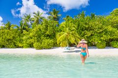 Beautiful attractive woman in bikini and hat walking on beach wooden jetty and luxury tropical sea view, luxury lifestyle royalty free stock photography