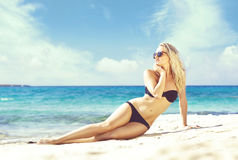 Beautiful and attractive woman in black bikini. Young girl posin. G on a beach at summer. Traveling, vacation, holiday, tourism, concept Stock Image