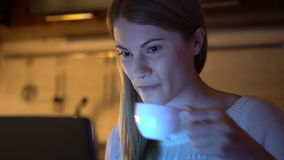 Beautiful attractive woman browsing internet and working on laptop. Evening Kitchen. Drinking coffee stock footage