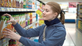 Beautiful attractive woman choosing packed juice in supermarket. Take pack from shelf, read labels.