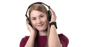 Beautiful attractive woman with headphones listens to music on smartwatch. Isolated white background. Beautiful attractive woman in pink dress with headphones stock video footage