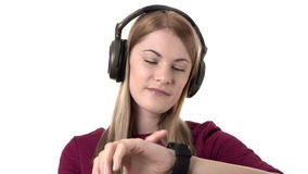 Beautiful attractive woman with headphones listens to music on smartwatch. Isolated white background. Beautiful attractive woman in pink dress with headphones stock footage