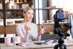 Beautiful attractive woman holding tone cream. Perfect skin. Beautiful cheerful pretty woman holding tone cream and make up brush and looking into the camera Stock Images