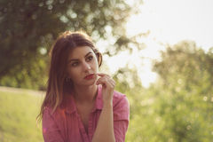 Beautiful and attractive woman landscape portrait watching at something. Wearing a pink shirt and multiple gold rings Royalty Free Stock Images