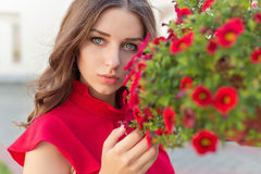Beautiful attractive woman with long hair in a red dress near the red flowers in the garden Royalty Free Stock Photography