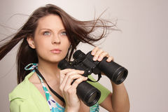 Beautiful, attractive woman looking through binocu Royalty Free Stock Photos